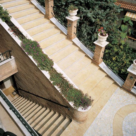 Scala esterna in marmo Giallo Reale con pavimentazione in Palladiana anticata in marmo Bianco di Carrara e fascia in Giallo Reale.