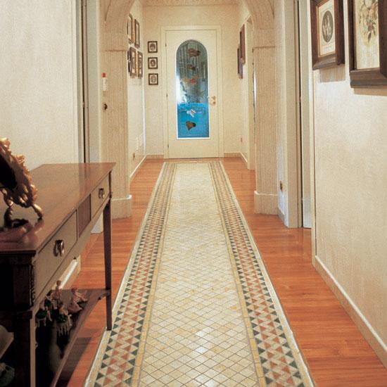 Ad impreziosire la calda armonia di un ambiente pavimentao con il parquet, l'intarsio a tappeto in Giallo Orientale 5x5 con greca in Rosso Asiago, Travertino, Giallo, Verde Alpi e Giallo Orientale