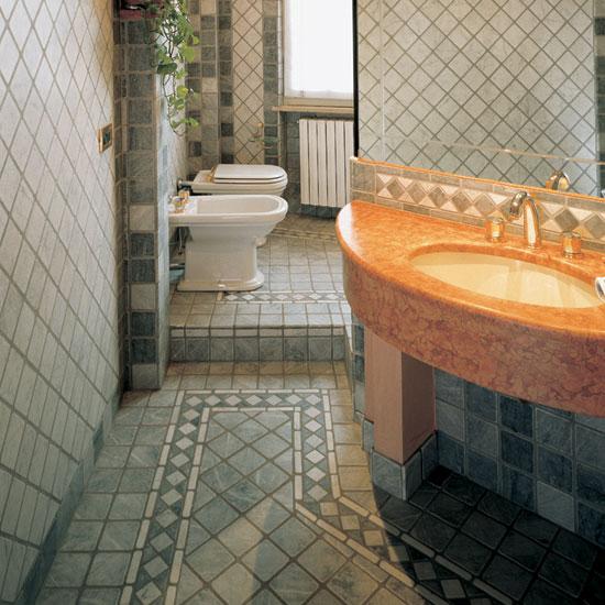 Greca in Bardiglio e Bianco Carrara ambientata nella stanza da bagno in ciottoli di Bardiglio e Bianco Carrara 10 x 10. Di particolare risalto il top in marmo Rosso Asiago semiovale.
