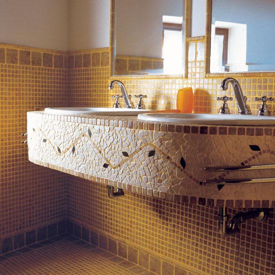 Pavimento e rivestimento stanza da bagno in mosaico Giallo Reale 2.5 x 2.5 e ciottoli 10 x 10 con listello tondo in Giallo Reale. Originale il top in mosaico Giallo Reale, Botticino e Verde Alpi.