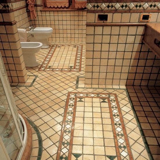 Stanza da bagno in Rosa Portogallo. Pavimento e rivestimento 10 x 10. Il tappeto in ciottoli di Rosso Asiago, Verde Alpi, Statuario e Rosa Portogallo ed i listelli differenziano il sistema di posa.