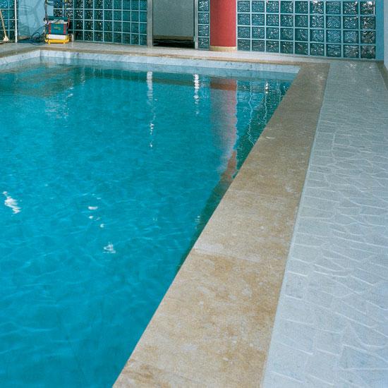 Pavimento esterno alla piscina in Palladiana Anticata di Marmo Carrara con Bordo in Giallo Reale. Il contrasto tra il bianco e l'azzurro è particolarmente evidente.