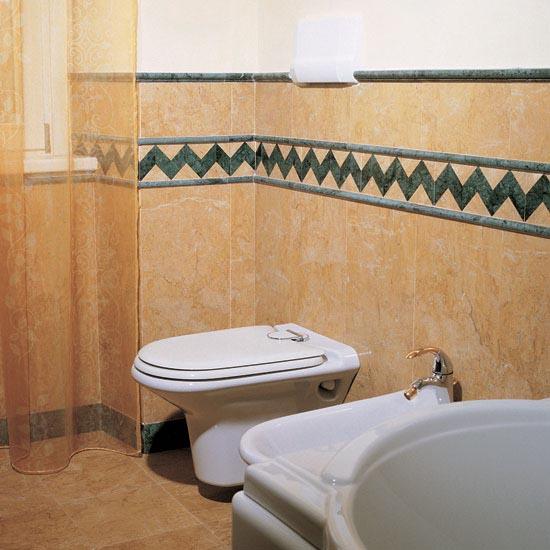Rivestimento stanza da bagno in Giallo Reale con greca e zoccolino Verde Guatemala