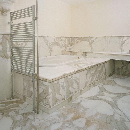Il marmo Calacatta, particolare per le sue venature e macchie che si incontrano tra un pezzo e l'altro, in una sala da bagno unica.