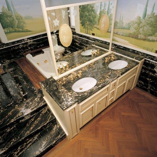 """Di straordinaria eleganza l'abbinamento del marmo Nero Portoro con il pavimento in legno. Il top con due lavabop sottopiano è finito con bordo a """"becco di civetta"""""""